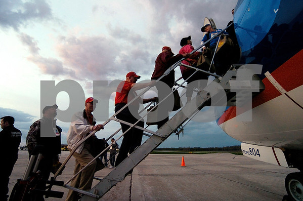 -Messenger photo by Hans Madsen<br /> <br /> Veterans and their guardians board the Brushy Creek Area Honor Flight early Saturday morning at the Fort Dodge Regional Airport. 99 veterans made the trip.