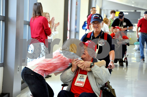 - Messenger photo by Peter Kaspari<br /> <br /> Army Veteran Johnnie Luppes gets a hug from Carol Owens, of Herndon, Va., as he disembarks from the flight at Dulles Airport.