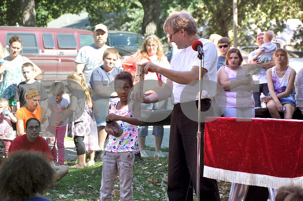"-Messenger photo by Joe Sutter<br /> <br /> Layla Nore, 7, of Fort Dodge, watches magician Larry Dunbar ""teach"" her a trick that only he can perform with pop bottles and cylinders during the Recovery and Wellness Family Fun Festival."