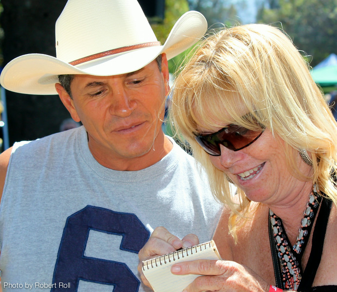 """Henry Engelking and Sherri Sanchez plot thier """"plan of attack""""-- deciding which of 28 different Chili booths to visit first at the third annual Camarillo Country Music Festival and Chili Cookoff."""