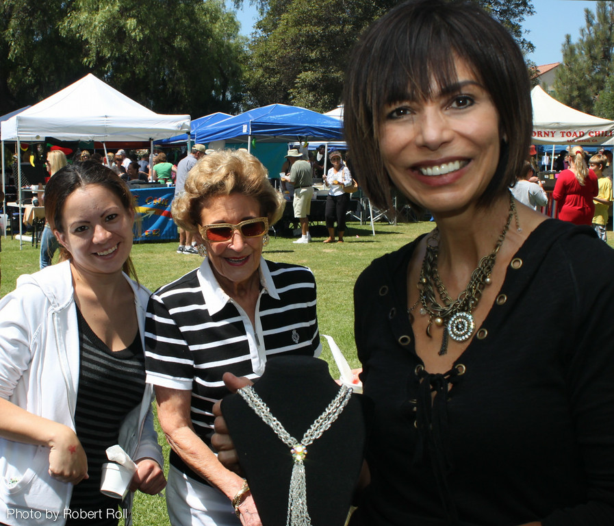Mariela Reynozo (left) of Santa Paula and Joyce Bradley of Santa Rosa Valley inspect a braided silver necklace from the studio of Amy Garcia Jewelry.  Garcia (right) was one of a score of artisans who participated in the Camarillo Country Music Festival and Chili Cookoff at Adolfo Camarillo Ranch.<br /> The event raised more than $60,000 for Camarillo Hospice, which hosted the event.