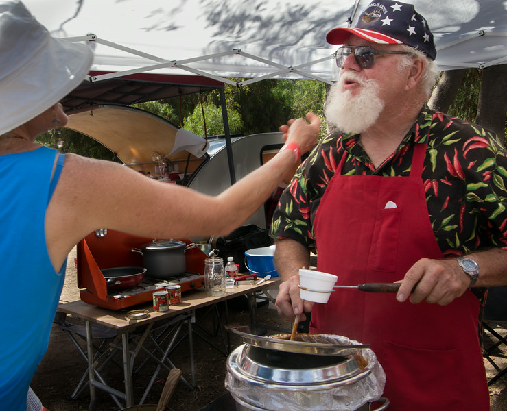 Howard Choate of Lompoc, CA assures a guest that his raffish chin-spinach is real as he dips into the pot of Buck 'N Bull Chili which has received multiple honors at Chili events nationwide.
