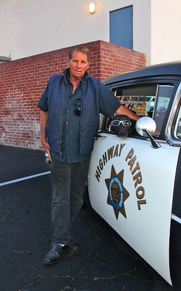 The Man Behind the Dog:<br /> Sargent Bono's chauffeur and best pal Lynn from Santa Paula takes a moment to confer with his police pooch.  Bono's favorite ride is this 1955 Buick decked out in full California Highway Patrol livery.