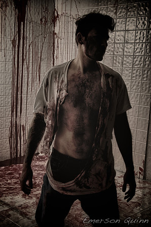 Man with torn shirt stands in the shadows of a bloody room
