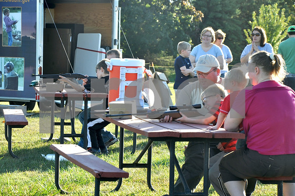 -Messenger photo by Joe Sutter<br /> <br /> Andy Stanberg, of Webster County Conservation, teaches his son Samuel Stanberg, 6, how to shoot a pellet gun at the annual Fall Park Festival at Kennedy Park. Kids could also try archery, tomahawk throwing, and atlatl. Samuel's brother Zachery and mom Cindy Stanberg are to the right.