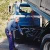 John M. Hill and his dump truck at daughter Beth's new house (1997). He built the dump body for this truck. Also notice his initials on the back of the cab.