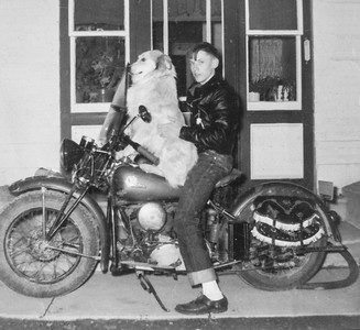 John M. Hill with his dog Schnippy. Schnippy used to ride with him on this motorcycle. John hid behind the dog going down the road so those passing by would look twice, thinking the dog was driving.