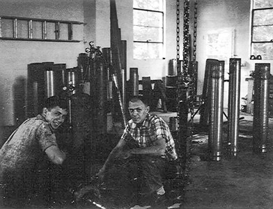 L-R: Dennis Haag (husband of Betty (Schrack) Haag) and John M. Hill (husband of Marie (Schrack) Hill). In John's hydraulic cylinder repair shop (now known as 'Shop 1'). Photo likely taken in the mid-1960's.