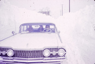 Marie (Schrack) Hill driving through the very deep snow banks, with her children Bart (left) and Beth (middle). Photo likely taken by her husband John L. Hill.