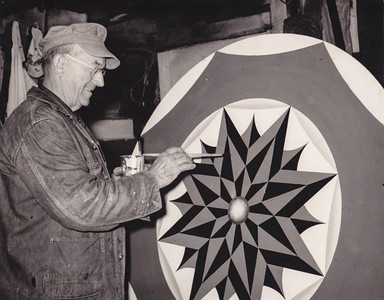 Milton J Hill at work, painting 'hex' signs.