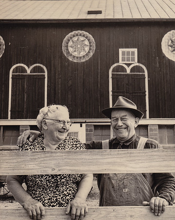 Gertrude (Strausser) Hill and Milton Hill, infront of their barn, with barn stars 'hex' signs that he painted. She had to stand in the trough to see over the fence.