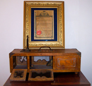 Milton J. Hill's mouse trap, with his Canadian patent displayed behind, dated Nov. 26, 1907.