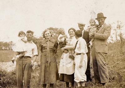 From left: Anna Schrack held by Bill Becker, Vera (Naftzinger) Schrack, Wayne Schrack (Jr.) being held by Mollie (Henne) Naftzinger, Ray Becker (looking backwards, son of Bill), Wayne Schrack (with light hat and dark suit), John Schrack being held by Joseph Naftzinger.  (Photo taken by Luella Becker - Vera's cousin).