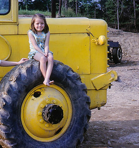 Beth Hill (later Humma) on the wheel of her father's (John's) payloader.