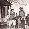 Wayne & Vera (Naftzinger) Schrack with children from left: Anna, Marie (blond front looking down), Peggy Naftzinger (dark hair, looking down), Wayne Jr. (back middle), Norman (front middle, with leg braces), Daniel, and John (far right). Photo taken at St Michael's church farmhouse around 1944-45.