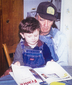 Charles with Ethan; both in farmers bibs looking at a farming magazine, all Ethan needs is a cap...