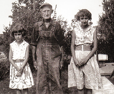 Marilyn and Leanna with their grandpa Charles, July 1957. Standing at pumpbed where Katie fetched water to do her washing and other needs.
