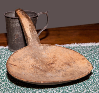 This is Katie's 'butter spoon' used to squeeze the butter milk out when making butter. Behind is a tin cup that Vera believes belonged to Wayne, Sr. from when he was a little boy at school.