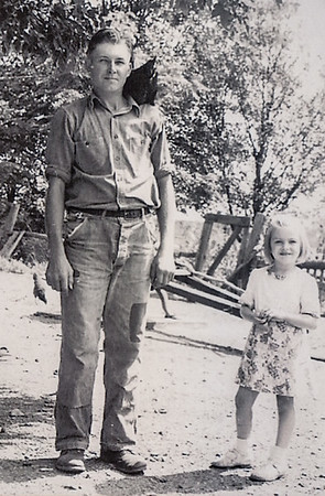 Earl R. Schrack with daughter Dolores, and a chicken on his shoulder.