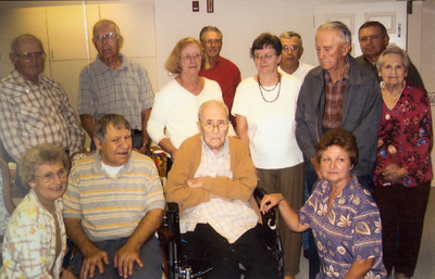 At John H. Schrack's 100th birthday Margo Langley asked all those born a Schrack to get in the picture... she didn't want to ask Vera to stand out. Front: Anna (Schrack) Reinhart, Norman Schrack, John H. Schrack, Betty (Schrack) Haag. Middle: John A. Schrack, Wayne Schrack, Mary Margaret (Schrack) Langley, Marilyn (Schrack) Kriener, Charles. Schrack, Vera (Naftzinger) Schrack. Back: Bob Schrack, Elmer Schrack, Michael Schrack
