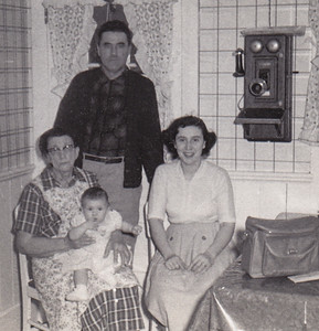 Four generations: Katie (Faust) Schrack, Roy Schrack, Mary (Schrack) Bender, and Debbie Bender. (Notice the old telephone hanging on Katie's kitchen wall.)