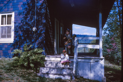Michael Schrack with nephew's and niece: Mike holding a nephew up-side-down, Bart W. Hill, and Beth Hill (later Humma) sitting on stairs of the hunting cabin.