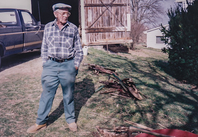 Wayne Schrack at his farm (Previously Faust farm, now John and Edna Schrack's farm). The white building in the back is the butcher shed.