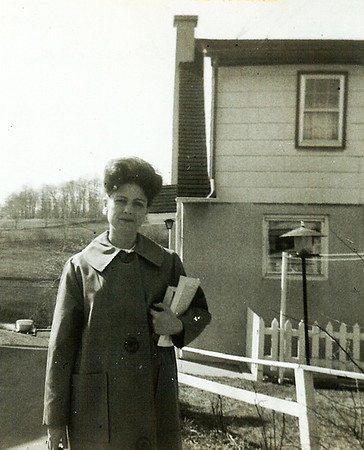 Marian (Werner) Humma behind her house, reading to go to the Kingdom Hall.