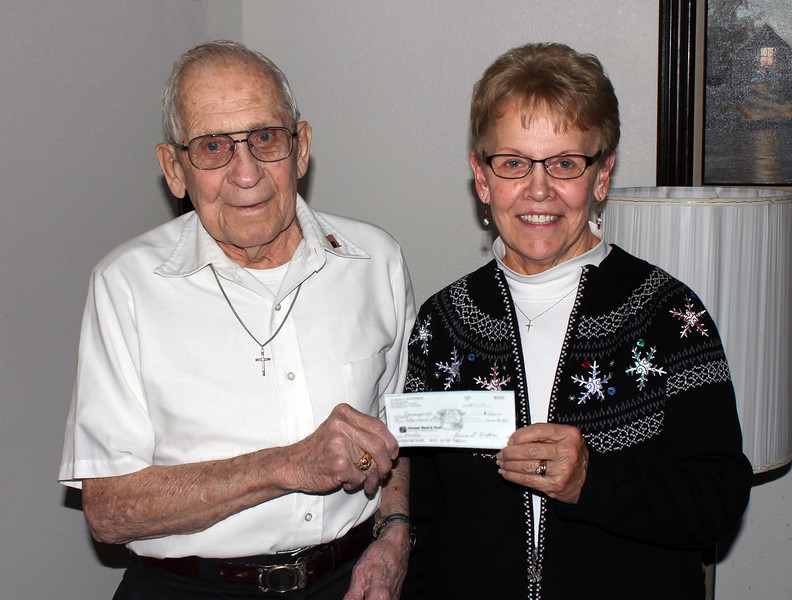 "<i>JUNIOR ANDERSON DONATES $1,000 TO PANTRY</i>  The Food Pantry was given a big boost this December (12/4/14) when long-time Spearfish resident Junior Andersen donated $1,000 to support pantry operations.   Andersen and his late wife, Betty owned and operated Andersen's Carpet and Drapery on Jackson Street for many years. <i>""I like giving back to the community, and supporting the food pantry seemed to be one good way to help do that,</i>"" said Andersen, seen here presenting a check to pantry vice-president Karen Miller.    <i>""Mr. Andersen's generosity is very much appreciated and will help so many families who rely on the Spearfish Pantry for support.  He has our deepest gratitude!""</i>"