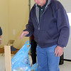 Volunteer Perry Beguin weighs one of the early-arriving bags of food during the 2011 Scout Food Drive in Spearfish.