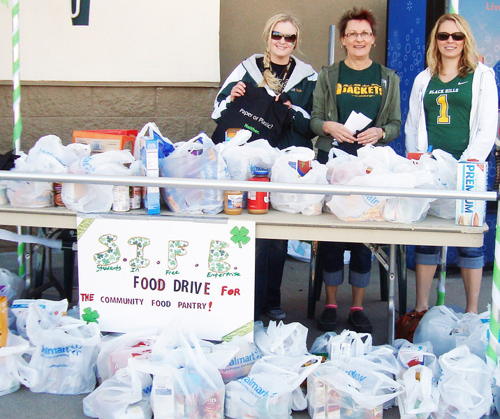 Jessie Cronk, Dr. Barbara Looney (SIFE advisor) and Jessie Jamptgaard from Students in Free Enterprise at BHSU pose behind a bevy of food collected during their March drive.  We are told that there are about 14 BHSU students who participate in <b><i>Students in Free Enterprise</i></b>.