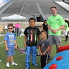 A teenage volunteer and children of various ages stand in front of an obstacle course.