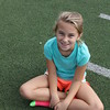 A girl sits on the field and smiles.