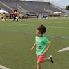 A boy runs across the football field.