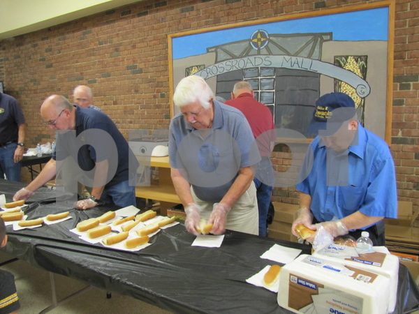 Golden Kiwanis Club members Nick Conrad, Clayton Evenson, and Arnie Clausen serve hot dogs to attendees at Kidzmania.