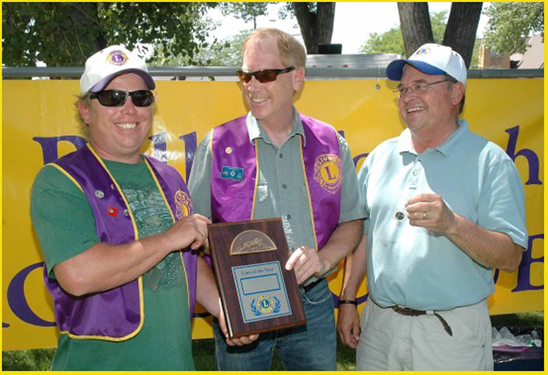Lion Rik Bartels (left) receives his <b><i>Lion of the Year </i></b> plaque during the the All Car Rally in June 2012.  Club president Brian Kline (center) and past president Ron Ensz participated in the presentation.  Both said they have enjoyed working with Bartels, who has been actively engaged in many projects.  He has served as club Secretary and has just finished a term as Vice President.   He'll take over the helm of the Belle Fourche Lions Club during the coming year.
