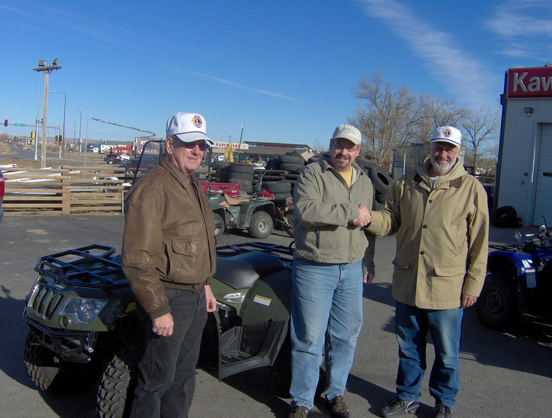Lion Tom Nary (right) congratulates Brian Haivala of Spearfish on winning an All-Terrain Vehicle as part of a fundraiser.  At left is Brian's dad, Lion Harry Haivala of Belle Fourche.