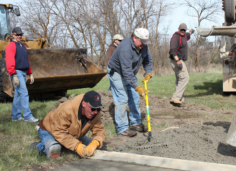 Men -- and women -- at work.  That's Susan Peterson at left, joining the assembled group that help pour concrete pads for the course.  Susan and a committee of other Belle Fourche citizens have been instrumental in helping bring a wide variety of enhancements to the concrete pathway around town.