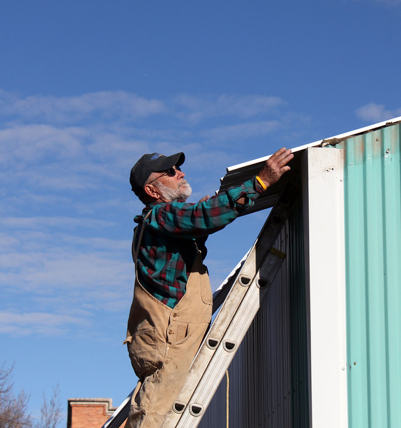 "Lion Osloond fits a piece of new fiberglass roofing in to place.  Thanks to all the many Lions who had a hand in completing this project.             Return to <a href=""http://www.bellefourchelions.org/""><b><i>Belle Fourche Lions Club</i></b></a> web site."