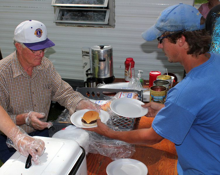"I'll trade you an empty plate for a burger!  Lion Leo Orme (left) serves burgers during the All Car Rally.  Thanks to Lions who helped at the All Car Rally events.  This was a successful event for the Belle Fourche Lions, netting more than $1,721.          <b>Return to <i> <a href=""http://www.bellefourchelions.org"">Belle Fourche Lions</a> web site</i></b>"