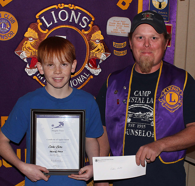 This is the second year in a row that Caden Kinter has been recognized for his good work.  Here, he receives his certificate and Second Place prize of $35 from Lions president Rik Bartels.