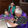 "Money in the making!  Lions treasurer Rich Drabek writes a check on behalf of the Belle Fourche Lions Club to give support to Junior Girl Scout Troop 70001's ""Operation Taste of Home.""<br /> <br /> LeeAna Best (seated at left) and Seyara Sechser (standing) watch as Lion Drabek does the deed!  An unidentified young man, meanwhile, keeps a wary eye on the photographer!"