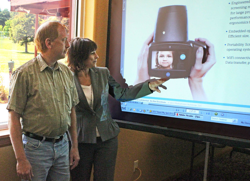 At a May 15, 2012 meeting at the Belle Fourche Country Club, South Dakota Lions Foundation Executive Director MJ Knobe gave a presentation that outlined plans for a statewide vision screening program for children.<br /> <br /> Knobe points to a bit of new technology from Pedia Vision that promises to help Lions in moving forward with the initiative.  Belle Fourche Lions Club president Brian Kline is at left.  <br /> <br /> The state foundation is awaiting word on a $59,000 grant from the Lions Clubs International Foundation that would help jump start the program.  It would allow Lions to purchase eight of the units for use across the state.