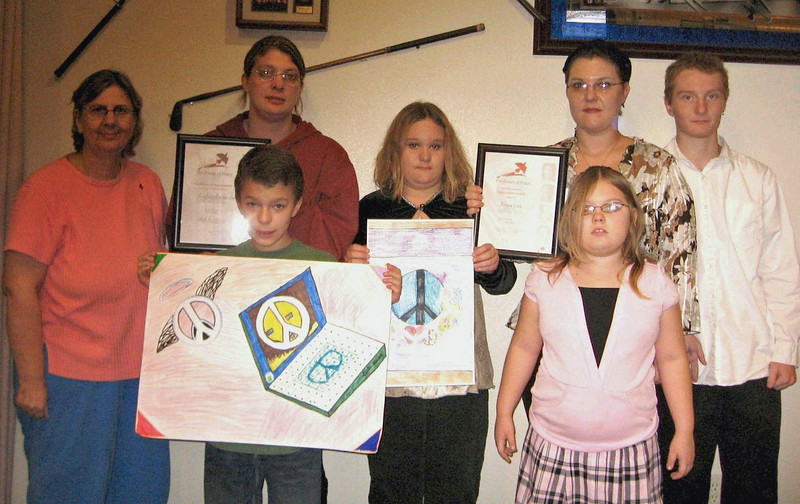 Shown here are the winners of the 2009 Peace Poster Contest and some of their family members.<br /> <br /> <br /> At extreme left is Kathy Messner of the Belle Fourche Middle School, adviser to the winning artists – First Place winner Adrian Erb (third from the left) and Second Place winner Tristan Barden (front row left). You may click on the photograph to see a larger image. Mrs. Messner, the winners, and their families were all dinner guests of the Belle Fourche Lions Club.