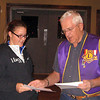 Lion Rich Drabek presents Liz Stairs with a $25 check for her second-place entry in the contest.