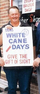 Lion John Cooper promotes the sale of white canes.  The proceeds of this project go toward helping sight-impaired persons.