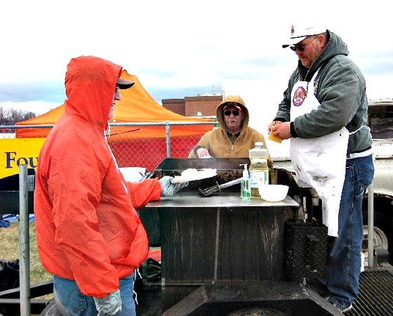 Lion Rick Walton dishes up a cheesburger for a chilly fan at a Belle Fourche High School track meet.