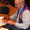 Lion Bill Kunerth inspects one of the several wooden bowls circulated during the meeting.