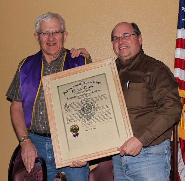 "Treasurer Rich Drabek and President Ron Ensz proudly display our club charter, which has been pulled ""out of mothballs"" and prominently displayed at the Belle Fourche Country Club."