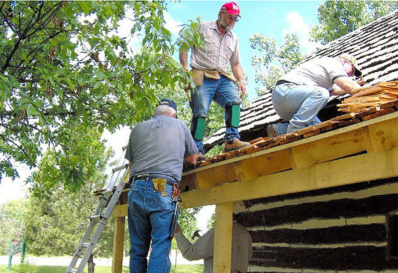 Belle Fourche Lions making roof repairs to the historic Johnny Spaulding cabin on the campus of the Tri-State Museum.  Shown (left-to-right):  Rich Drabek, Jim Osloond, and Rick Watson.